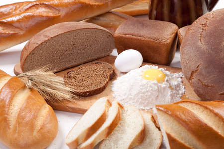 Fresh bread bakery products with eggs and flour on the breadboard photo