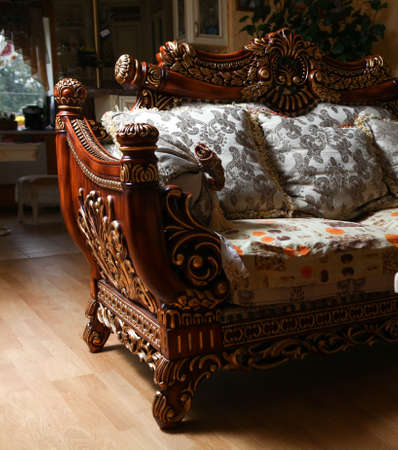 Carved antique luxury expensive sofa with cushions. Close up photo
