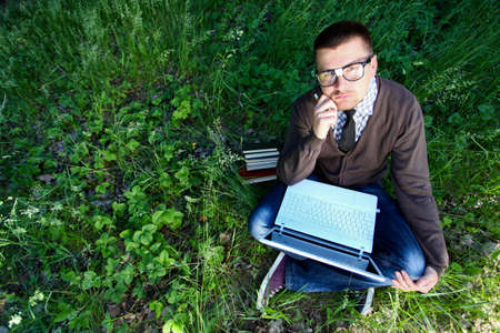 A man in glasses with a laptop and a raised thumb up sitting on the grass photo