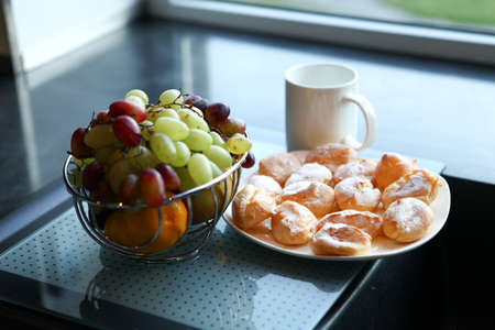 White cup, a plate of cake and fruit bowl stand on a glass table by the window photo