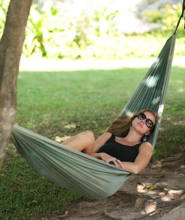 Beautiful young woman with sunglasses resting in a hammock in the shade photo