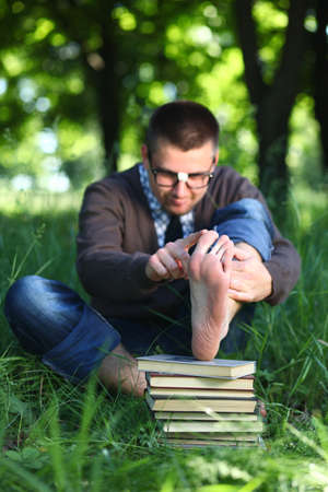 A man in glasses sitting on green grass with books photo