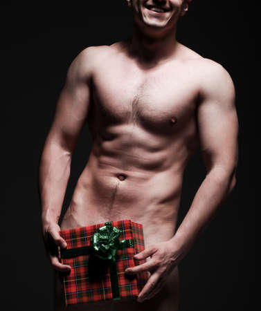 A bare-chested young man showing his abs with box in his hands Stock Photo - 14348974