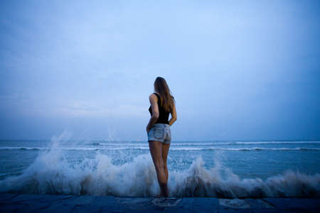 Woman standing back and watching the waves beating against the shore photo