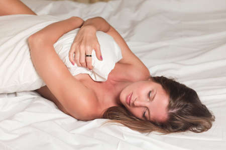 A young attractive woman lying on a bed with white sheets Stock Photo - 14349206