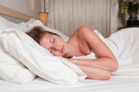 Una mujer joven y atractiva acostado en una cama con s�banas blancas Foto de archivo - 14726572