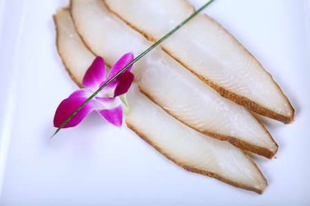 Fresh white fish decorated with spring onion and flower. Close-up photo