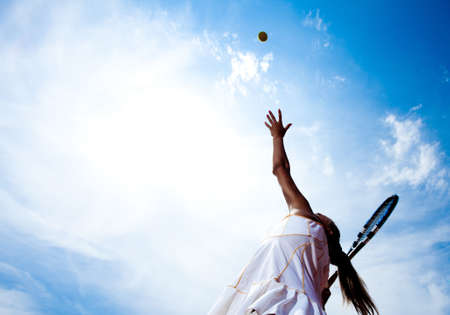 Tennis woman in a white tennis dress developing ball service Stock Photo