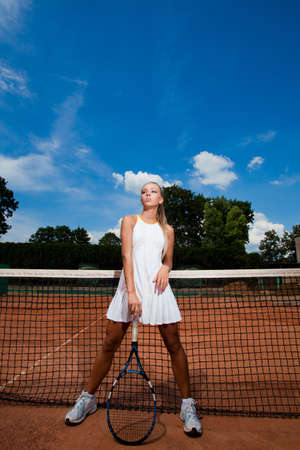 Beautiful athletic young woman in a white tennis suit leaning on the racket photo