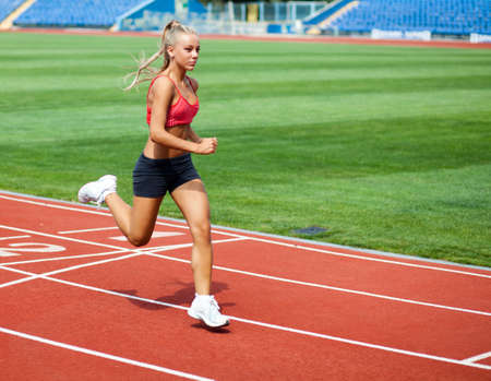 Beautiful young woman in a sports suit running on a treadmill at the stadium photo