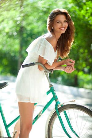 jeune vieux: Jeune femme dans une robe d'�t� blanche se penchant sur un guidon de v�lo vieux