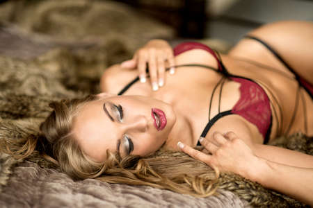 Smiling woman lying on bed in lingerie. Stock Photo