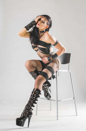 beautiful woman with bdsm accessory posing on the chair Stock Photo