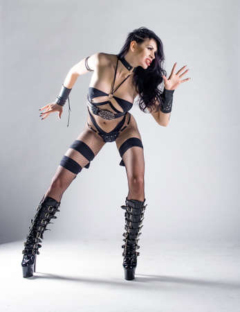 Beautiful woman model posing in studio. Wearing black leather bdsm sexy clothes. Costume for strap