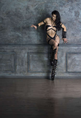 woman in fetish lingerie holding a whip in her hands and posing in front of an old wall