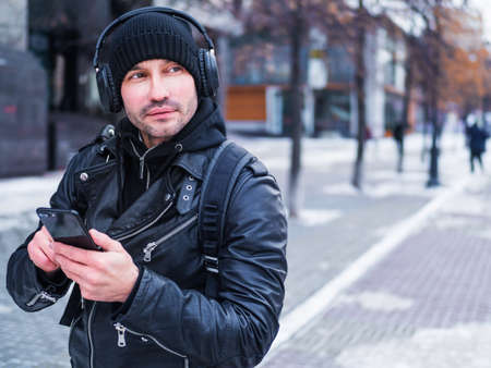 Man looking for a place using GPS map in smartphone. He lost in unknown city. he is dressed in a leather jacket, hat and headphones.