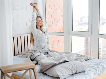 Adorable woman enjoying her morning and stretching in bed