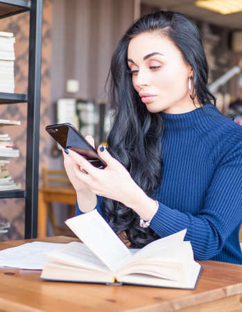 Beautiful woman at coffee shop. Person side view, send message by smartphone. Student reading books for exam in library, holding mobile phone.