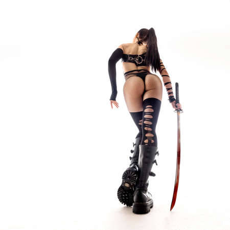 Sexy woman in anime uniform witha a katana sword. ciew from back Stockfoto