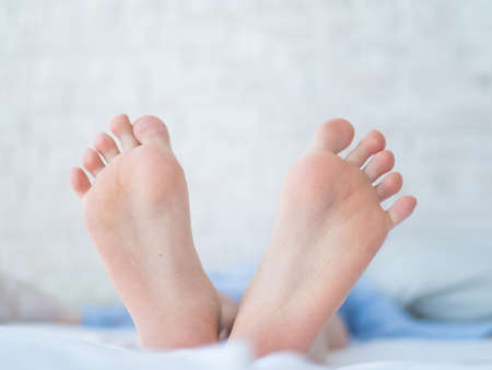 female feet, toes showing under the sheet Standard-Bild