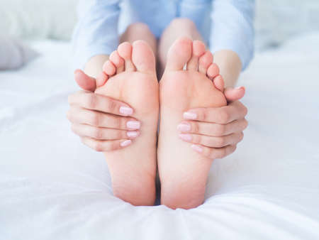 Young woman massaging her foot on the bed., Healthcare concept Archivio Fotografico