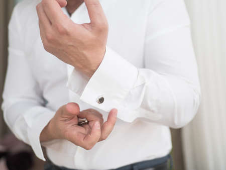 Groom is holding hands on the tie, wedding suit. close up of a hand man how wears white shirt and cufflink. Business man fixing black tie on white shirt. Groom on wedding day fixing tie, vintage