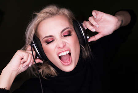 fasionable woman listening to the agressive music via headphones and sing on gark background Stock Photo