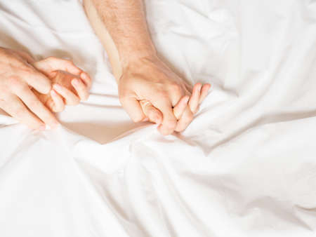 Sensual beautiful young couple is having sex on bed. Female hand pulling white sheets in ecstasy, orgasm. Love concept. Wellness. Couple in love. Orgasm concept Фото со стока
