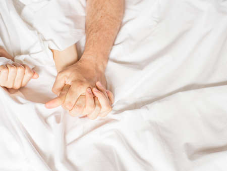 couple hands pulling white sheets in ecstasy, orgasm. Concept of passion. Orgasm. Erotic moments. Intimate concept. Sex couple. Bedroom. Hotel room. Spa. Vacation.