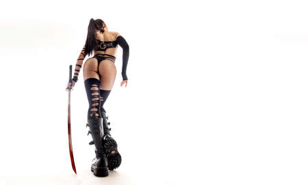 Sexy woman in anime uniform witha a katana sword. ciew from back Banco de Imagens