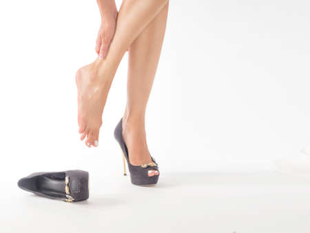 female feet in pain after wearing high heeled shoes.