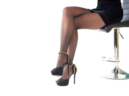 Sexy woman wearing high heels shoes and short skirt sitting in office chair. Isolated on white Фото со стока
