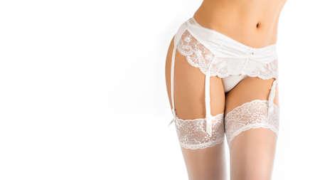 Nahaufnahme des weiblichen Körpers in den Strümpfen und im Stützgürtel lokalisiert auf Weiß
