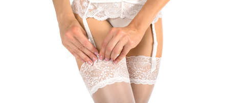 Close-up of female body in stockings and support belt isolated on white.