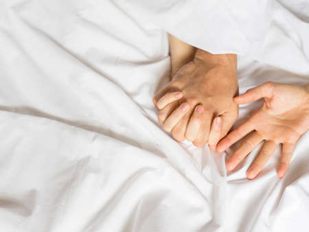 couple hands pulling white sheets in ecstasy, orgasm. Concept of passion. Orgasm. Erotic moments. Intimate concept. Sex couple. Bedroom. Фото со стока