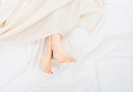 Female feet under blanket flat lay. Female beautiful feet with red pedicure on the bed. Top view on the sleeping woman legs under blanket