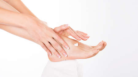 Frau, die Creme auf ihren schönen Füßen aufträgt.