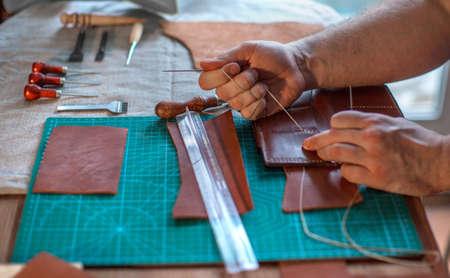 Verarbeitungsprozess des Ledergürtels in der Lederwerkstatt. Mann, der Handwerkswerkzeug hält und arbeitet. Gerber in alter Gerberei. Holztisch Hintergrund. Nahaufnahme des Mannes Standard-Bild