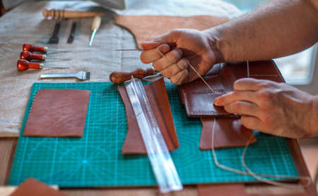 Working process of the leather belt in the leather workshop. Man holding crafting tool and working. Tanner in old tannery. Wooden table background. Close up man arm Stockfoto