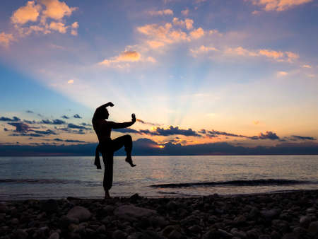 Silhouette of a man practises wing chun on the beach