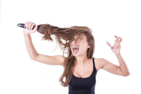 Young woman screaming while comb out tousled brown hair by brush. Isolated on white background