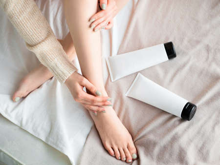 Woman putting ointment or moisturizer cream on her legs. Skin care