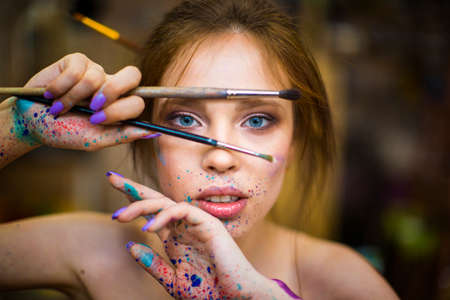Close up portrait of beautiful female artist with dirty hands with different paints on them, holding paint brushes near her face and eyes.