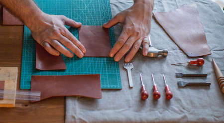 Working process of the leather wallet in the leather workshop. Mans hands holding crafting tool