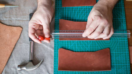close up Man hands working with leather using crafting DIY tools
