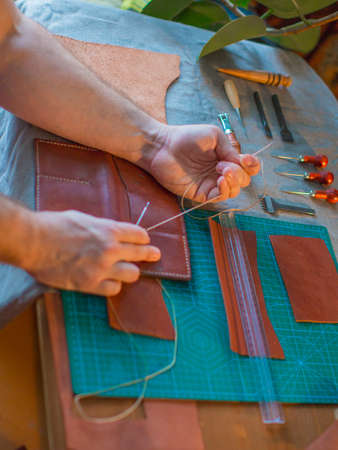 stitching a leather parts in a workshop. Handmade leather craft concept