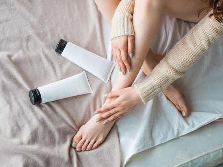 Piernas femeninas y tubo de crema hidratante en la cama. Concepto de cuidado de la piel