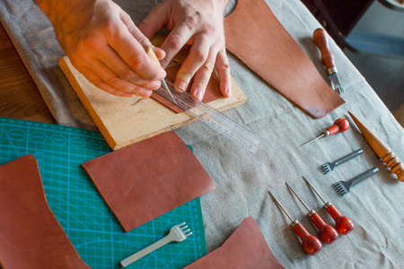 Working process in the leather workshop. Man holding crafting tool and working. He is sewing to make a walet. Tanner in old tannery.