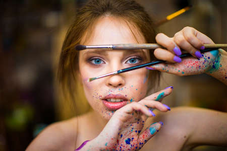 portrait of artist woman with a drops of paints on her face Imagens