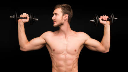 european caucasian athletic man bodybuilder holding dumbell and showing his muscular arms